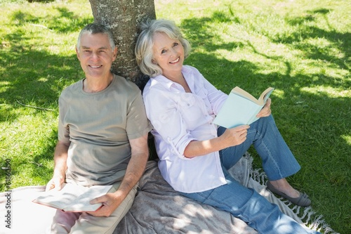 smiling mature couple sitting against tree at park