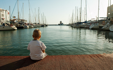 Little boy sits alone in the port