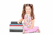 Cute little girl sitting next to a stack of books