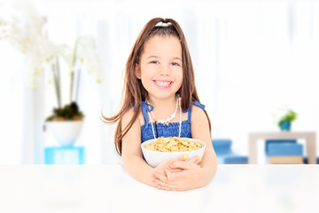 Cute little girl eating a bowl of cornflakes seated at table