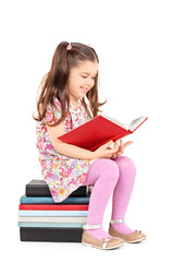 Female child reading a story seated on stack of books