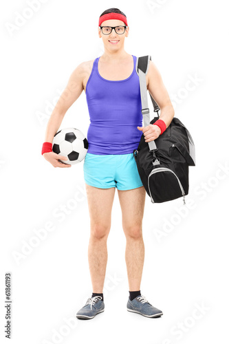 Young athlete with sports bag holding football