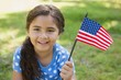 Young girl holding the American flag at park - 61862182