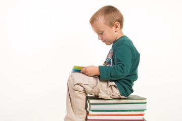 enfant assis sur pile de livres