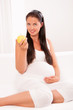 Beautiful pregnant woman on sofa eating an apple