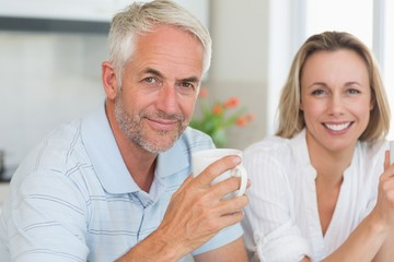 Happy couple having coffee together looking at camera