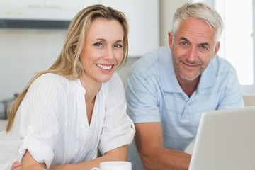 Smiling couple using laptop together at the counter