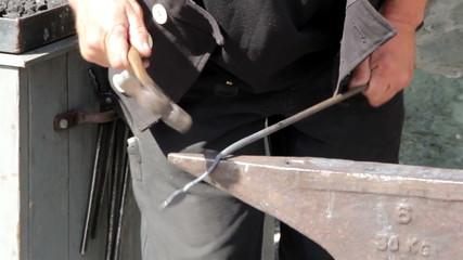 A blacksmith bending hammering of a metal or steel