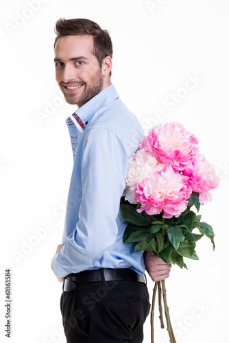 Man hiding a flower behind his back.