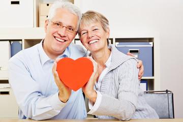 Paar Senioren hält rotes Herz