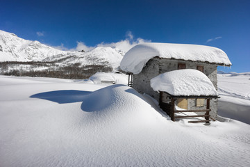winter landscape, hut covered with snow in the mountains