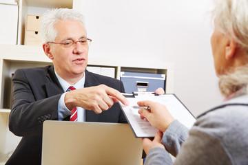 Frau bekommt Beratungsprotokoll nach Beratung in Bank