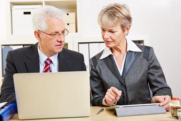 Geschäftsleute im Büro vergleichen Computer