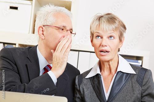 Mann flüstert Frau Geheimnis ins Ohr
