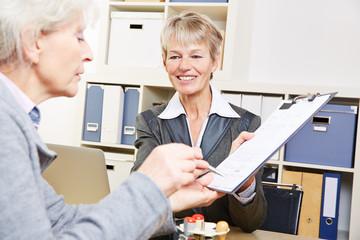 Seniorin in Bank unterschreibt Vertrag