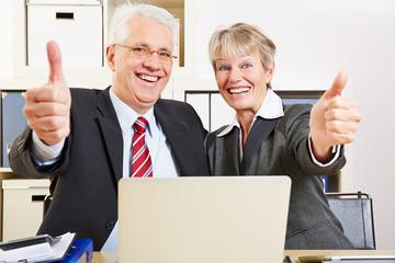 Zwei Senioren im Büro halten Daumen hoch