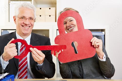 Geschäftsleute mit Schlüssel und Schloss im Büro