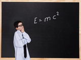 child in front of the blackboard thinking to solve the formula