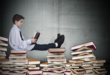 boy sitting on stacked books studying with a book