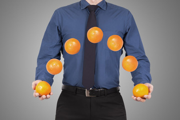 Businessman with tie juggling oranges, business concepts