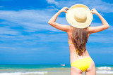 back view of beautiful young woman in bikini and hat standing on