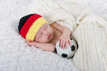 Newborn mit Deutschlandmütze und Fußball