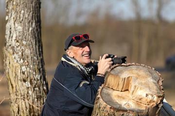 Mężczyzna w starszym wieku fotografuje przyrodę.