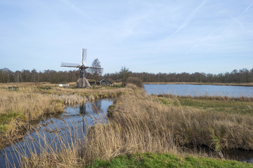 Windmill along a stream through wetland