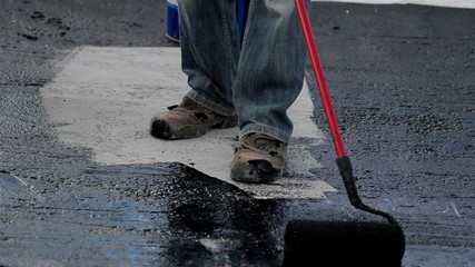 Road men applying asphalt on the small part of the highway