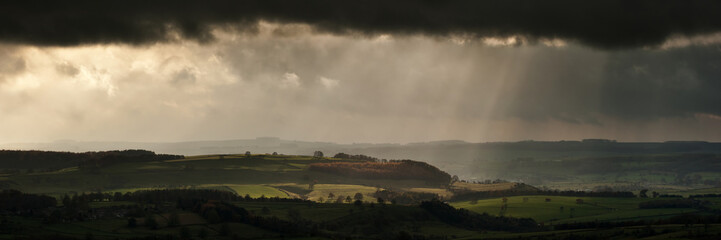 Panorama landscape dramatic sky with sun beams over countryside