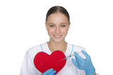 Smiling doctor with a syringe pricks heart symbol