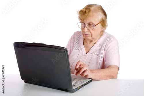 granny in glasses looks at the screen notebook on a white backgr