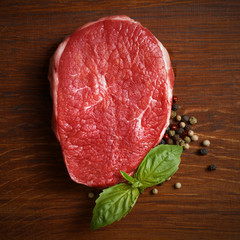 fresh raw steak with pepper and basil