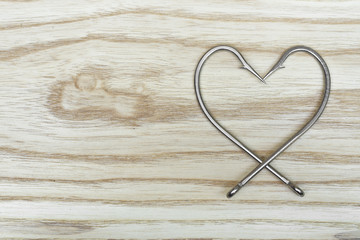 fish hook arranged as a heart shape on wood texture
