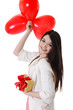 Smiling girl with red balloons and gift
