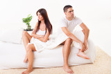 Angry Young couple sitting on the bed
