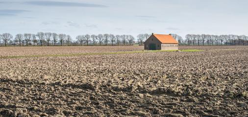 Old barn in a plowed field