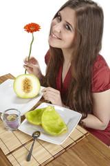Junge Frau am Esstisch mit Schalen einer Galiamelone