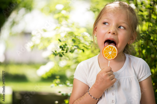 Little Girl in the Park with orange Lollipop.