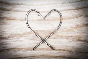 fish hook arranged as a heart shape on wood background