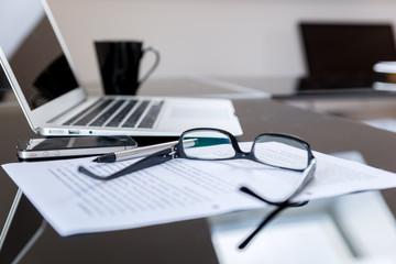 Arbeitsplatz mit Laptop, Notizen, Brille und Kaffeetasse