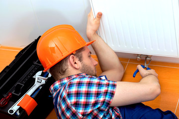 Handy man repairing heater