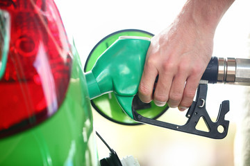 Gas station pump - filling gasoline in green car