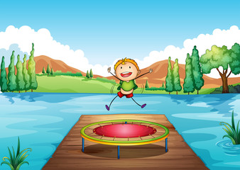A boy playing with the trampoline at the river