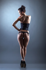 Rear view of sexy model posing in erotic lingerie