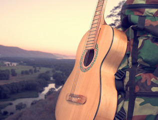 Landscape with a backpack and a guitar
