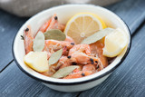 Enameled bowl with boiled shrimps over wooden surface, close-up