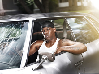 cool african man in car wearing wife beater and dew rag
