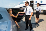 Pilot Helping Elegant Woman Stepping Out Of Car