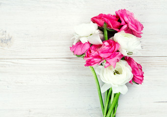 pink and white ranunculus flowers on woode surface